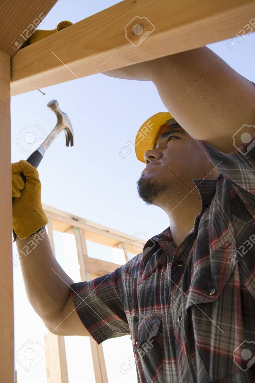 Construction worker hammering nail on construction site Stock Photo - 5470456