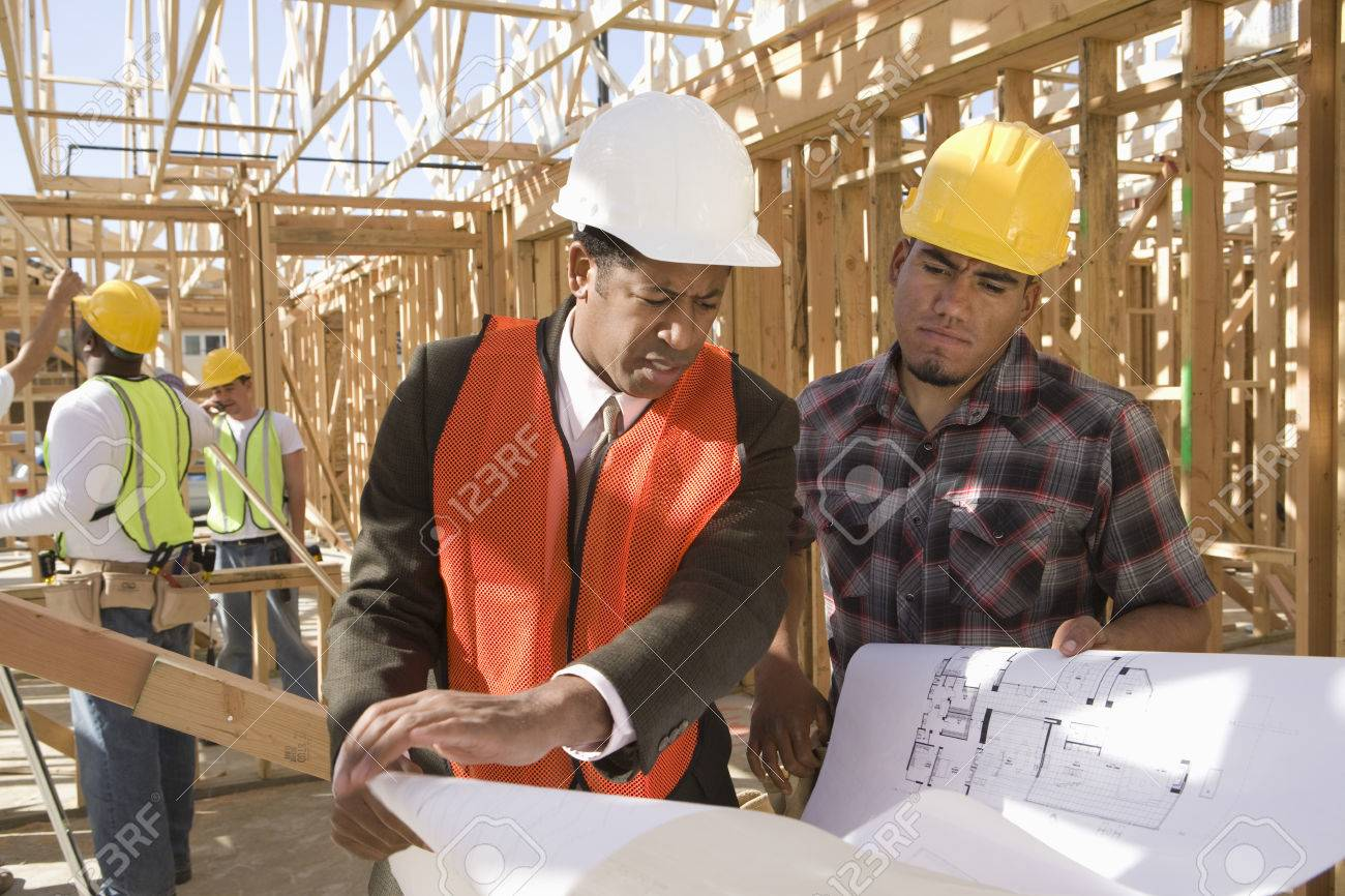 architect and construction worker looking at blueprints stock