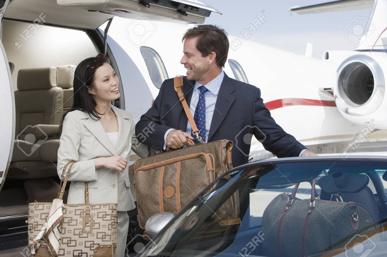 Mid-adult businesswoman and businessman getting in car. Stock Photo - 5475018