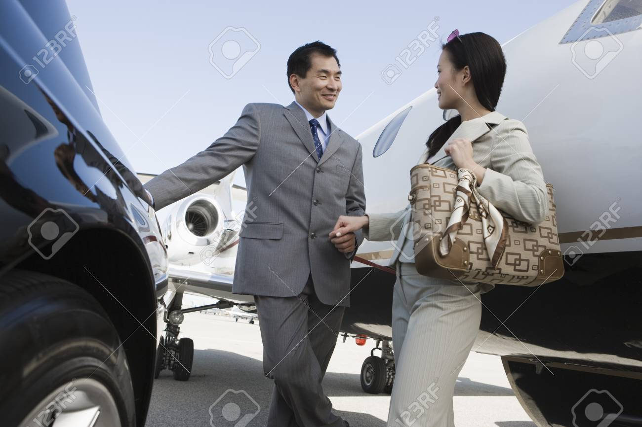 Mid-adult Asian businesswoman and businessman flirting outside of car and airplane. Stock Photo - 5475036