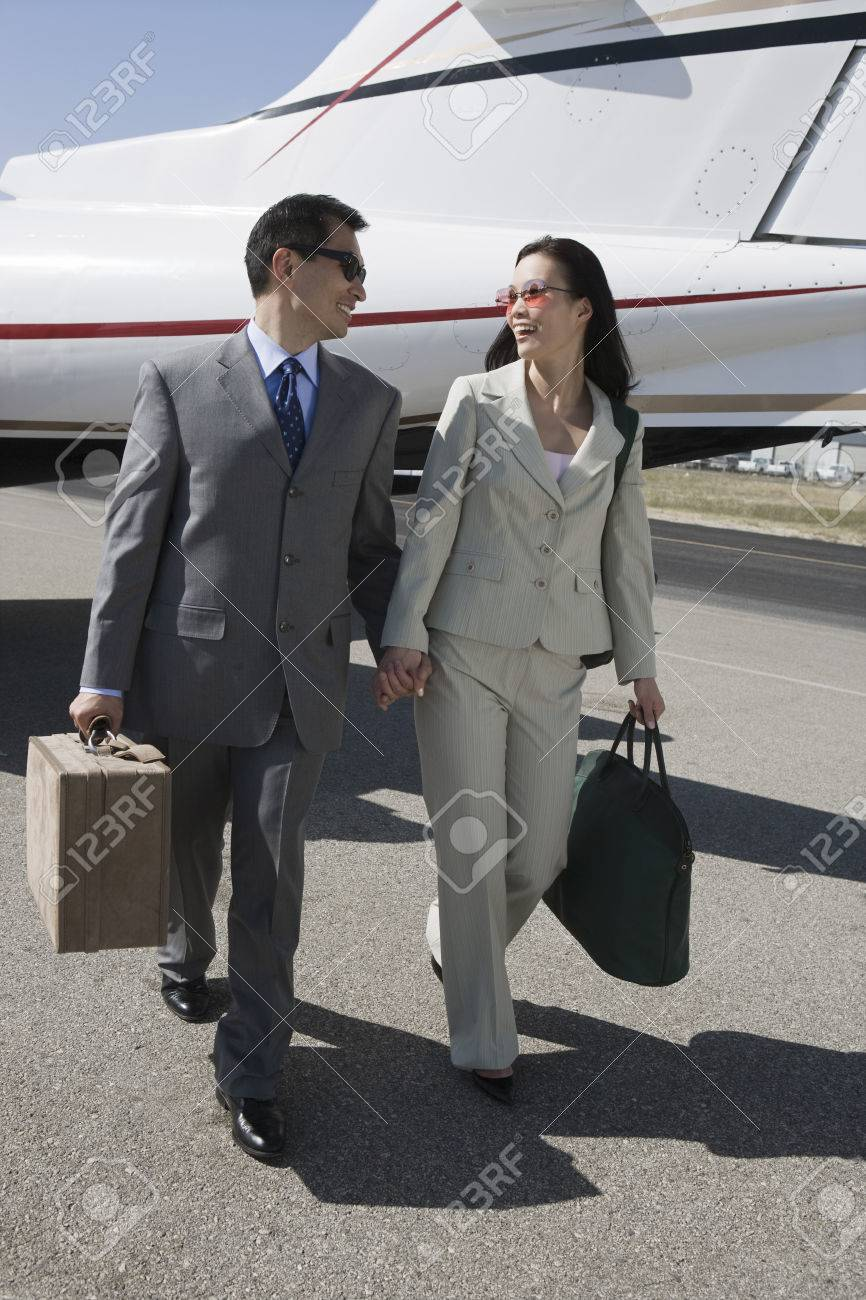 Mid-adult Asian business couple walking in front of airplane. Stock Photo - 5475038