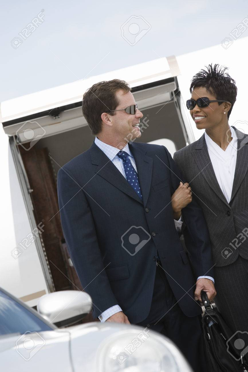 Mid-adult businesswoman and businessman in front of airplane. Standard-Bild - 5475064