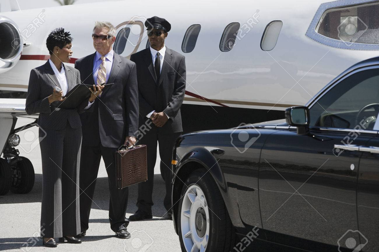 Mid-adult businesswoman, senior businessman and chauffeur in front of private airplane. Stock Photo - 5475073
