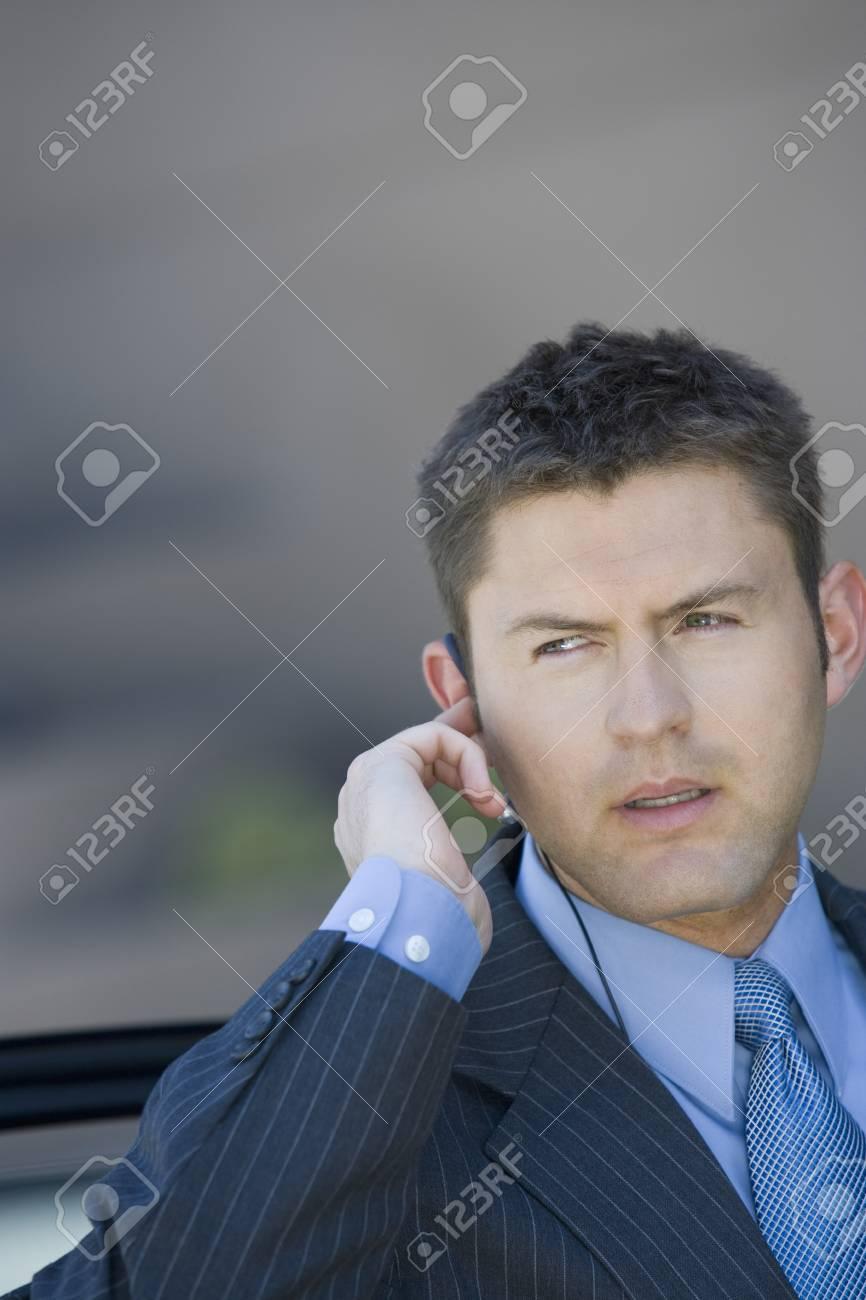 Business man wearing earpiece, outdoors Stock Photo - 5475417