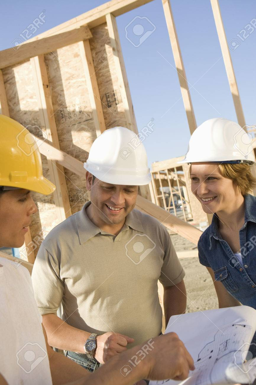 Two men and woman with blueprints at construction site, portrait Stock Photo - 5412263