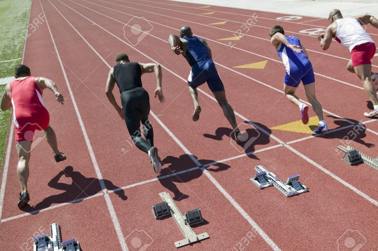 Male sprinters leaving starting blocks Stock Photo - 5475772