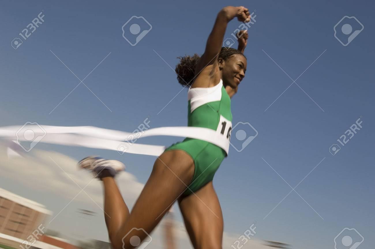 Female track athlete crossing finishing line Stock Photo - 5476016