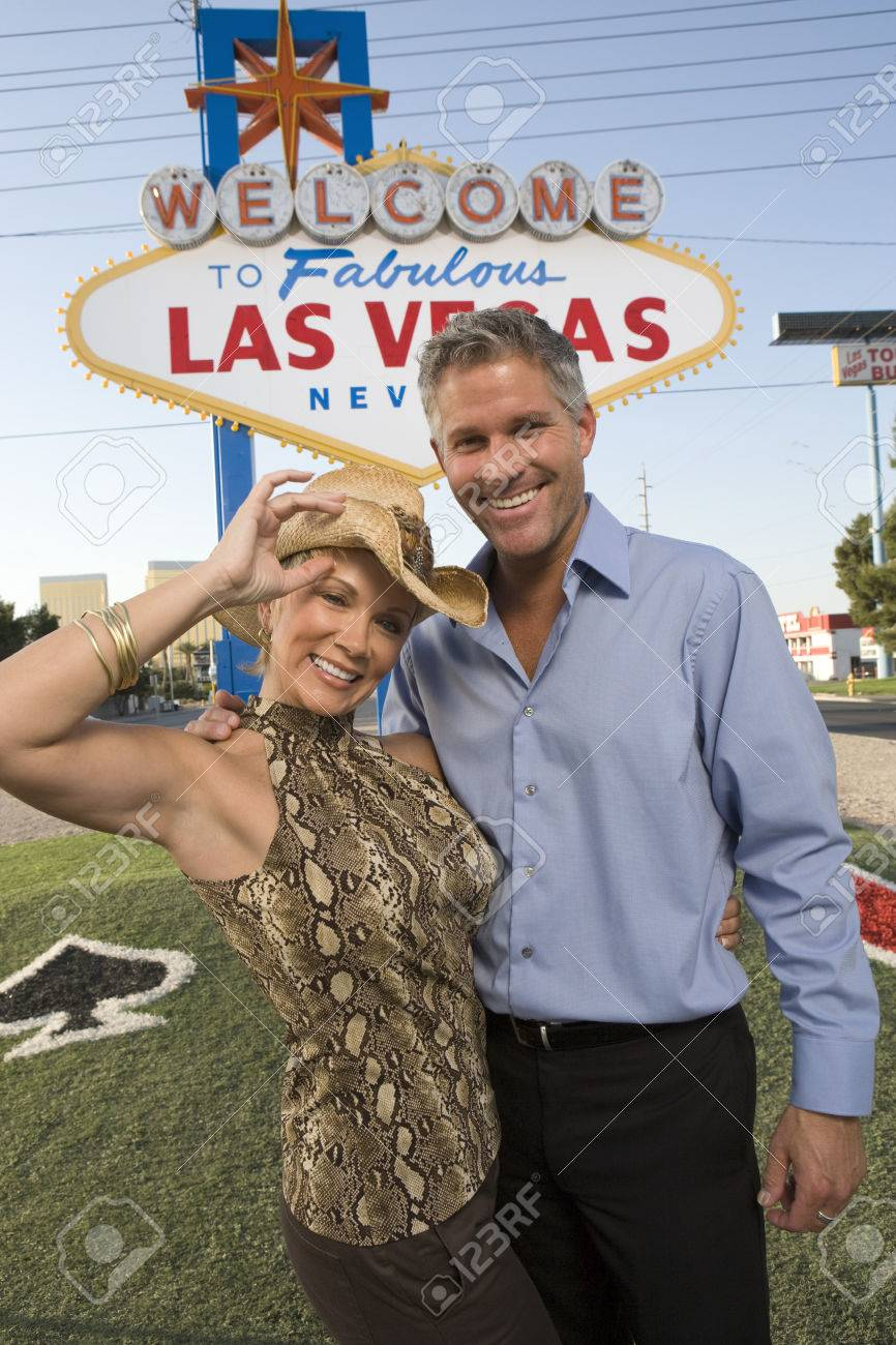 Middle-aged woman and mid-adult man in front of Welcome to Las Vegas sign, portrait Stock Photo - 5476301