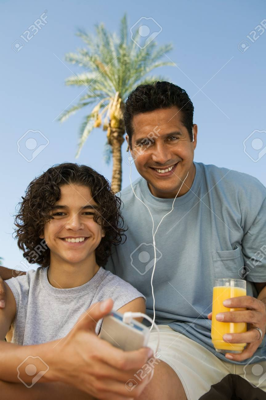 Boy (13-15) holding portable music player father listening with earphones an holding glass of juice front view portrait. Stock Photo - 8822635
