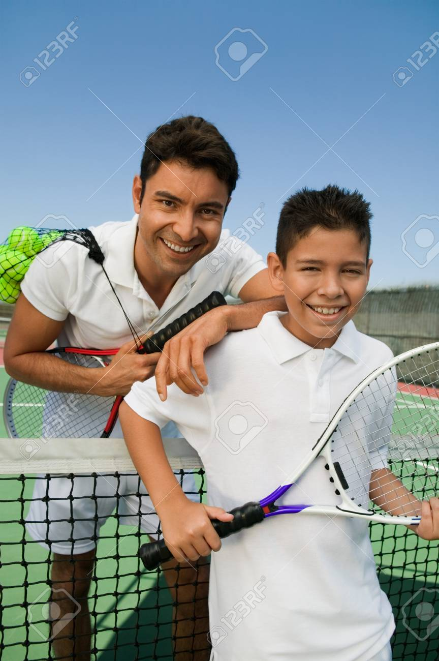 Father and son standing at net on tennis court portrait Stock Photo - 8822750