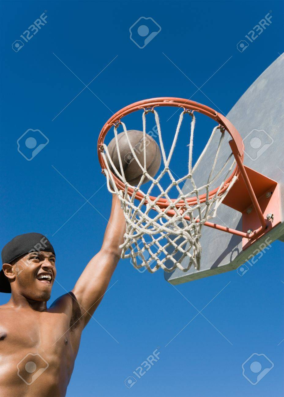 Young man dunking basketball into hoop Stock Photo - 8836259