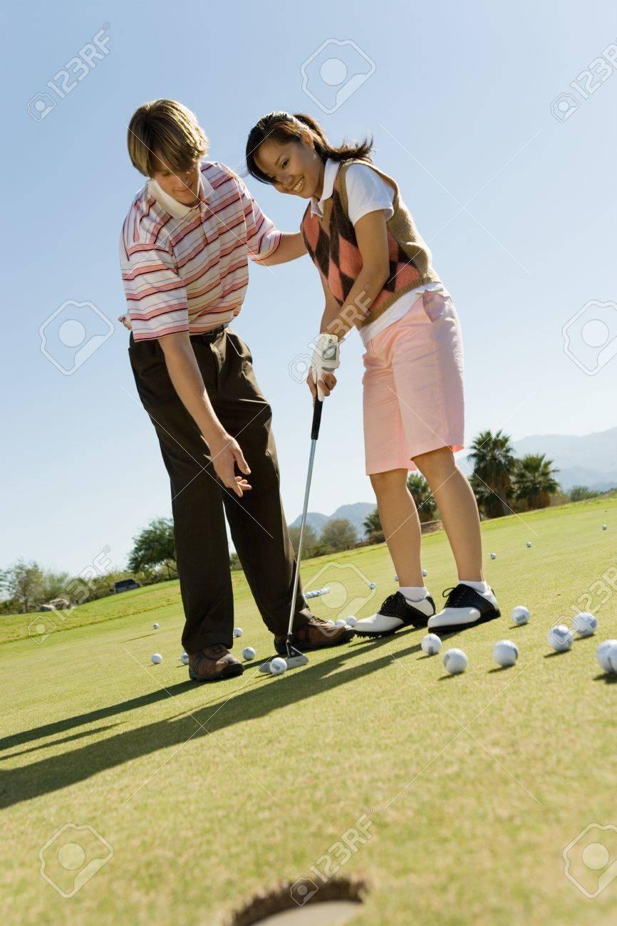 Man teaching teenage girl to putt Stock Photo - 8836485