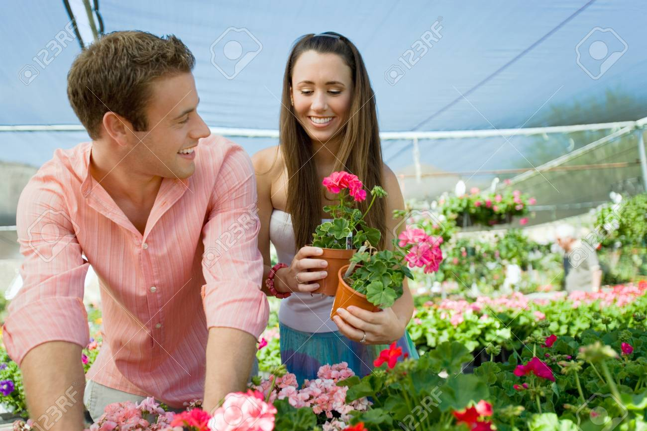 Young couple choosing potted flowers in garden center Stock Photo - 8837023