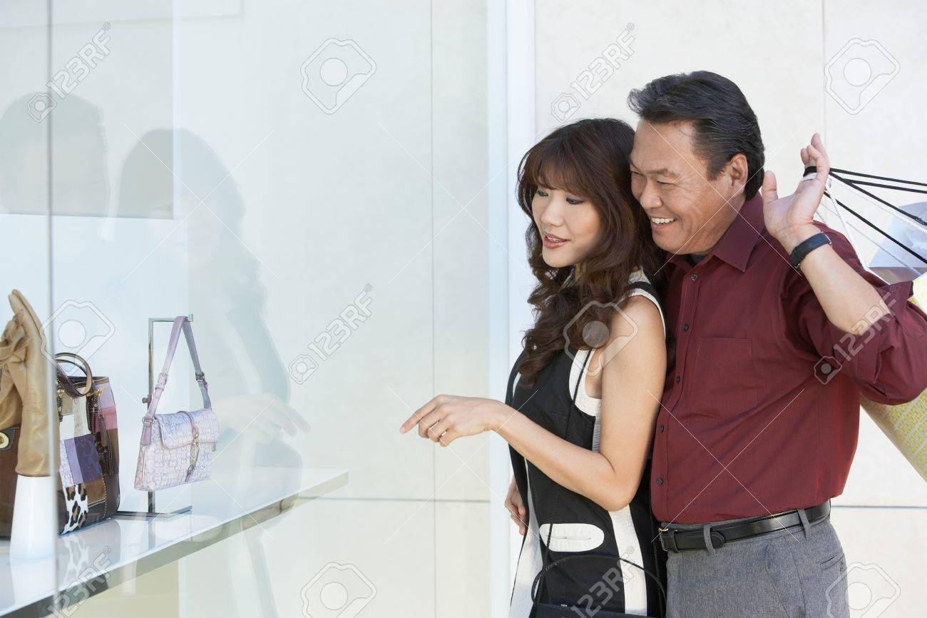 Couple looking at merchandise in shop window arm around holding shopping bags Stock Photo - 8837054