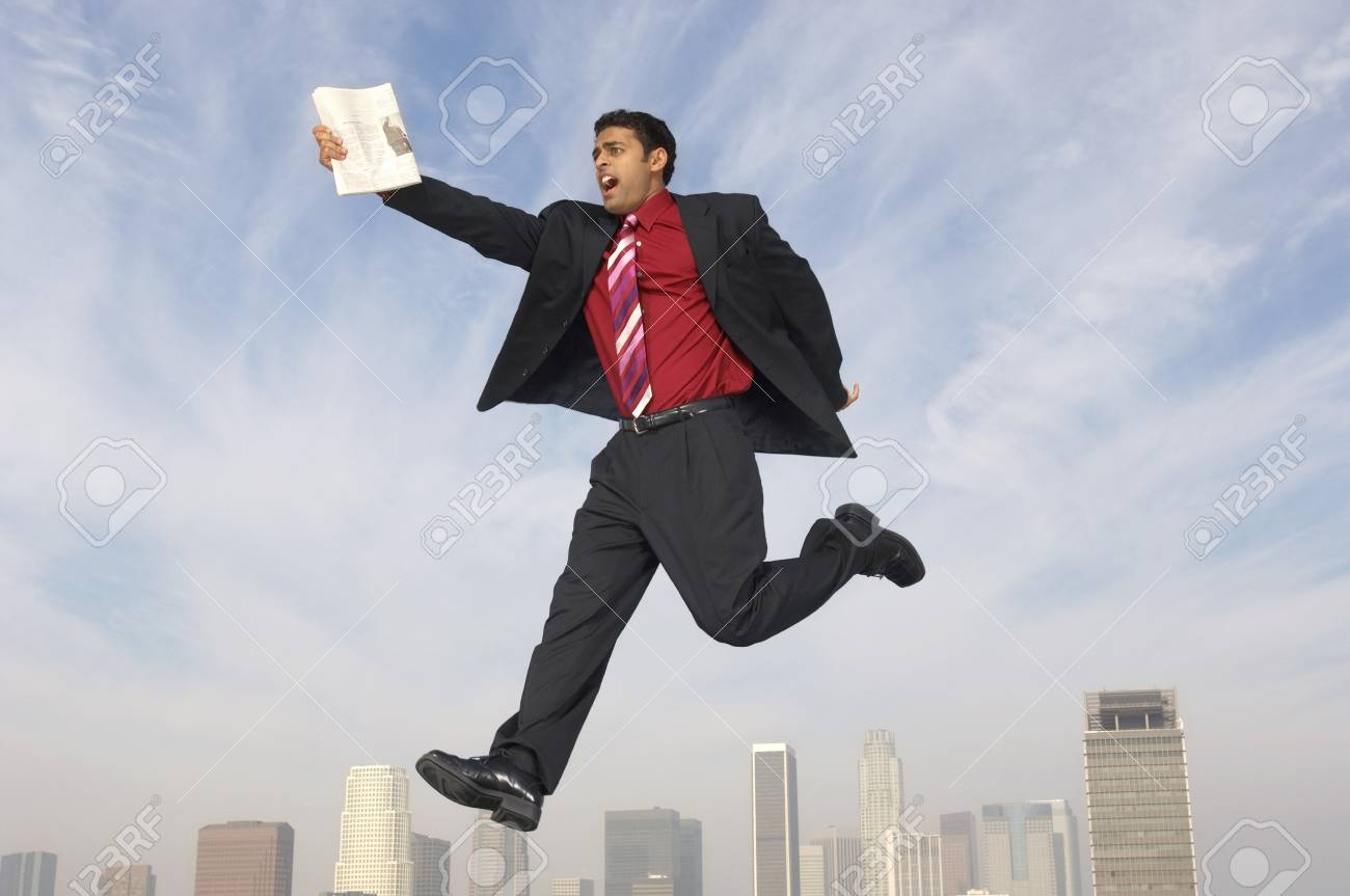 Business man jumping with newspaper over city Stock Photo - 8822515