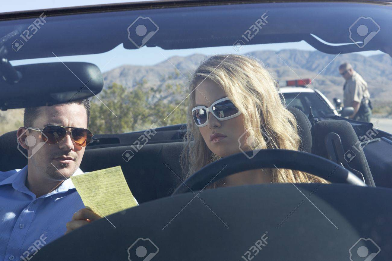 Couple sitting in car looking at traffic ticket Stock Photo - 8837486