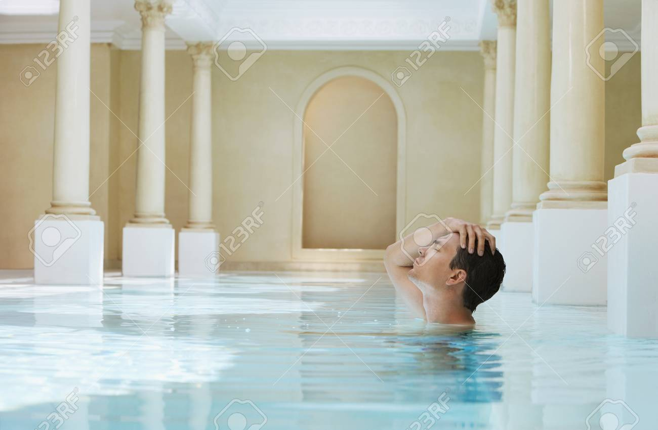 Young man with hand on head in swimming pool side view - 8844898