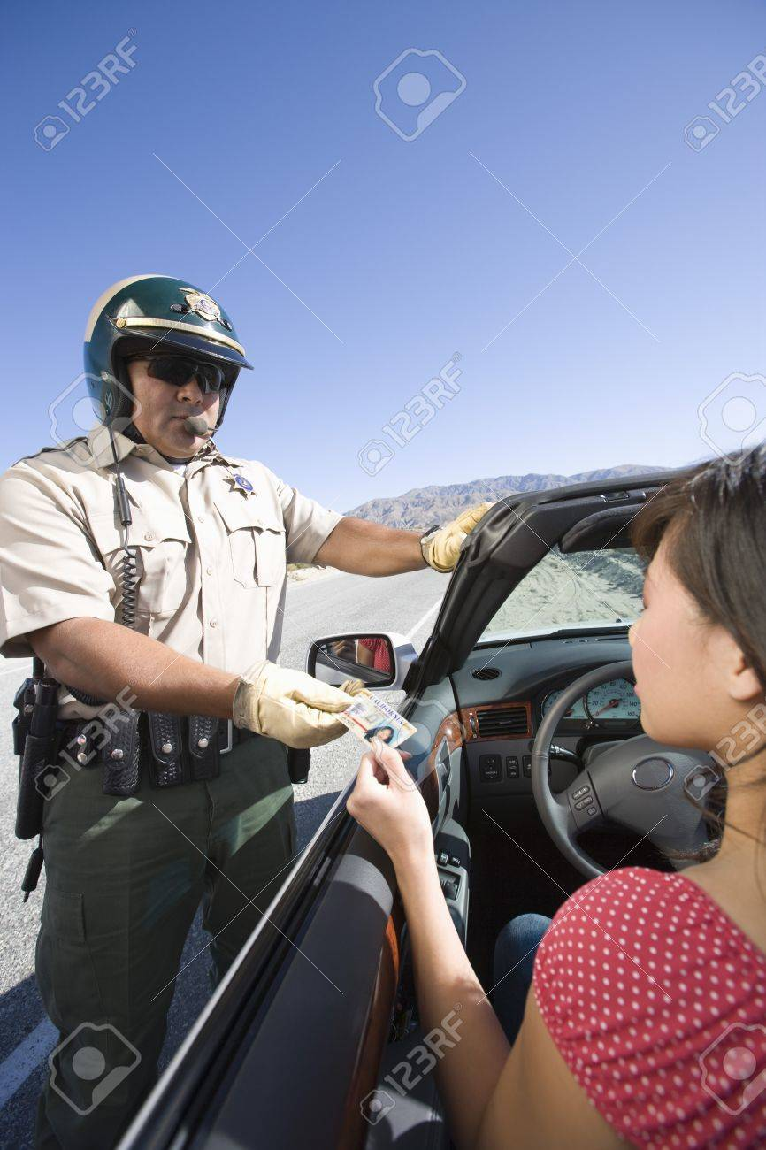 Police officer checking driver's ID Stock Photo - 12513676