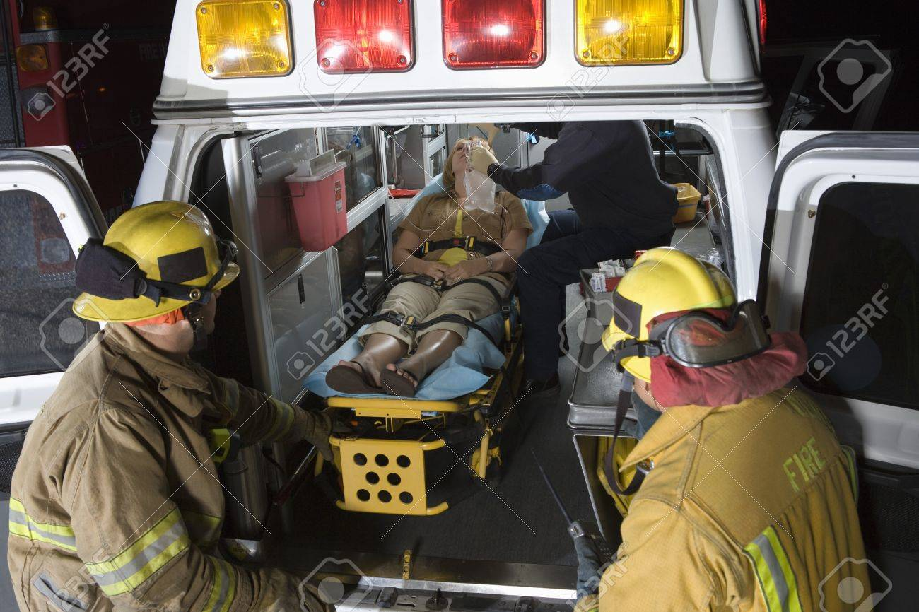 Firefighters looking at victim in ambulance Stock Photo - 12513758