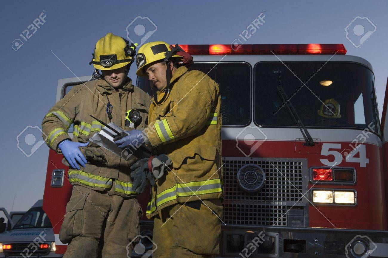 Firefighters planning rescue by fire engine Stock Photo - 12513783