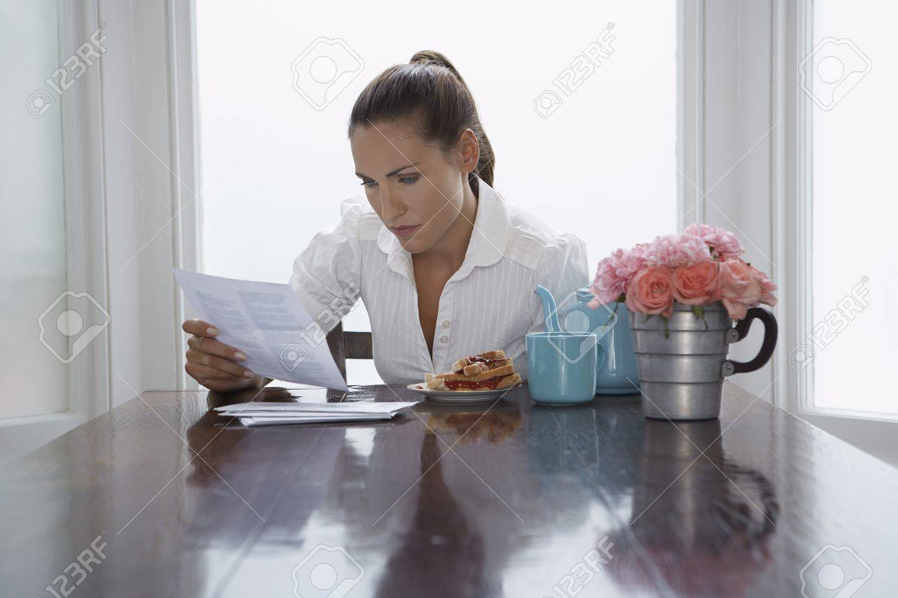Woman reading at dining room table Stock Photo - 12513993