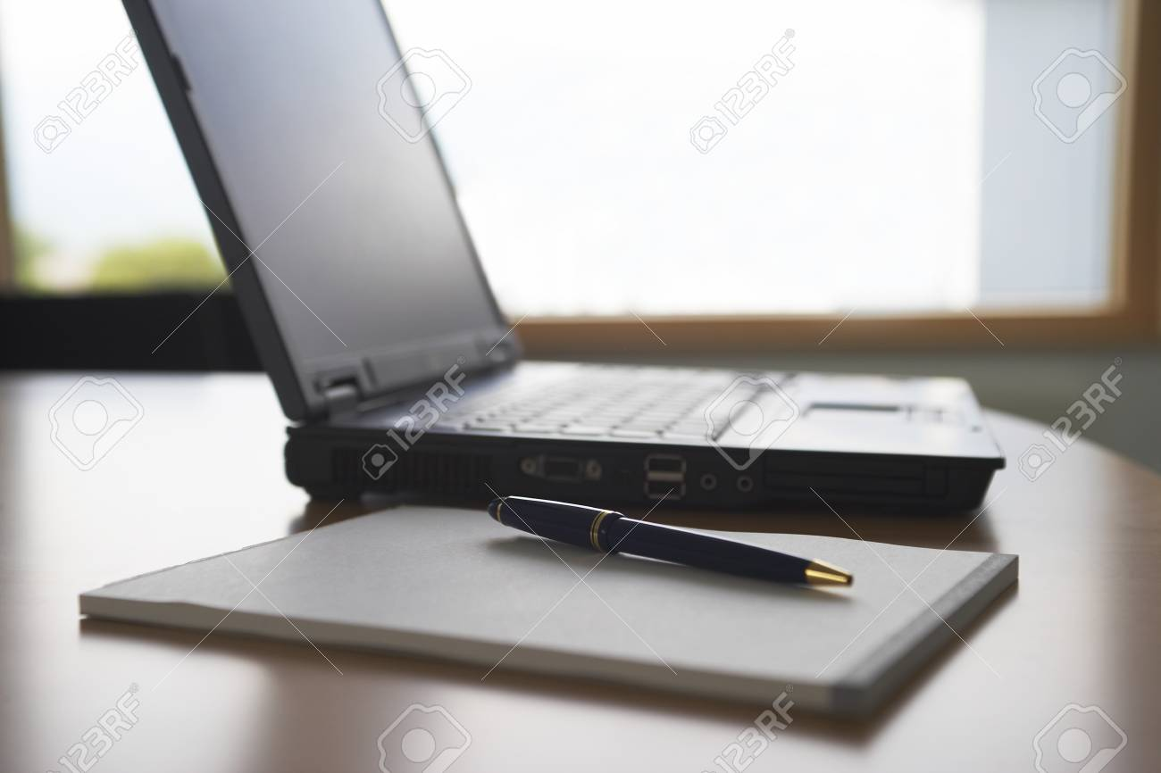 Laptop and notepad on desk Stock Photo - 12513999