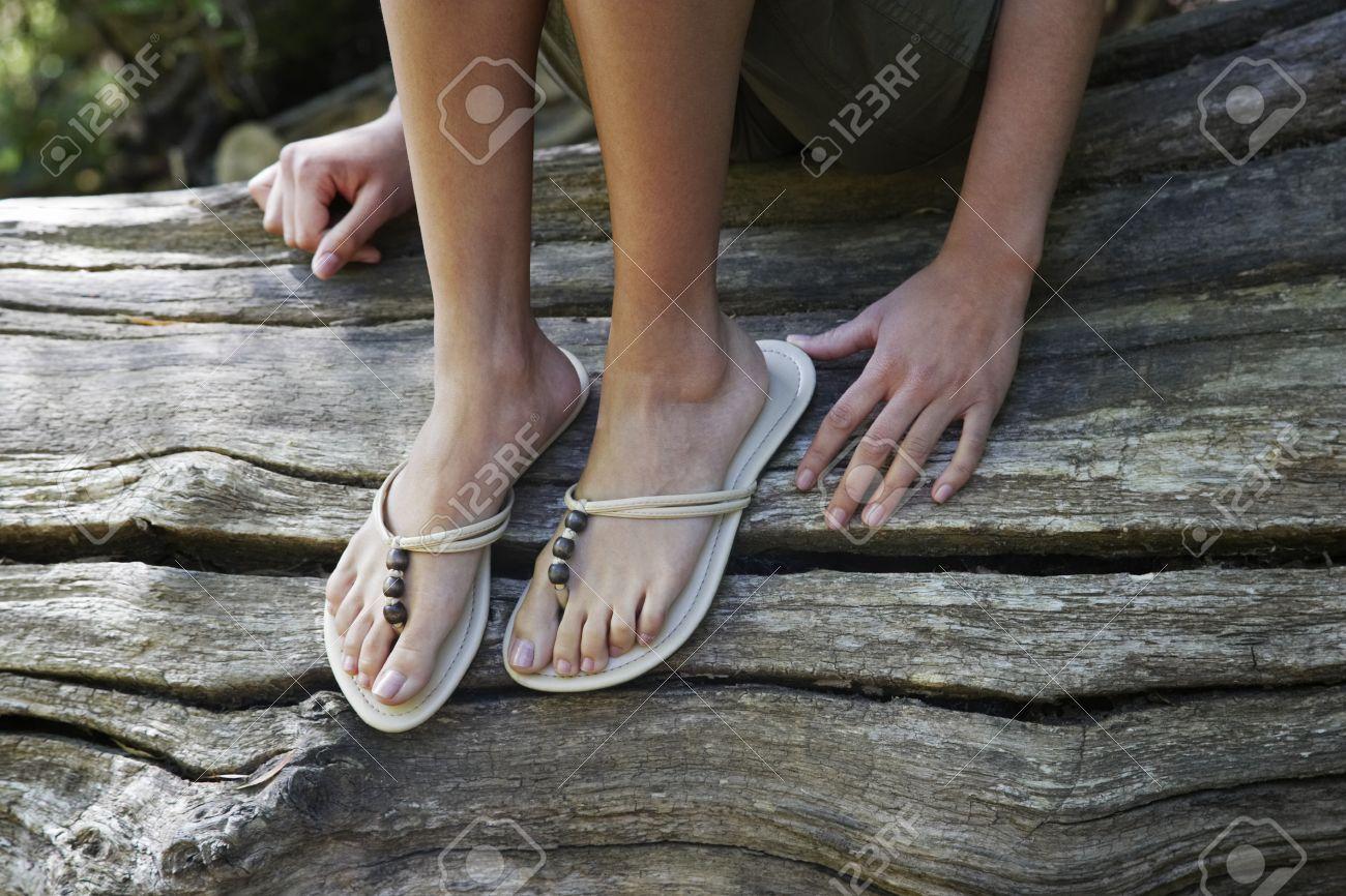 Teenage girl (16-17 years) wearing flip-flops sitting on tree trunk low section Stock Photo - 12514210