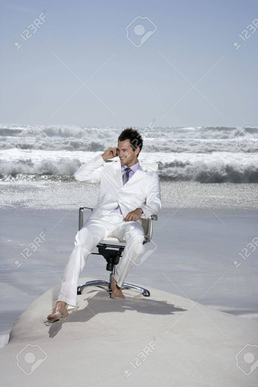 Man using mobile phone sitting on office chair on beach Stock Photo - 12514226