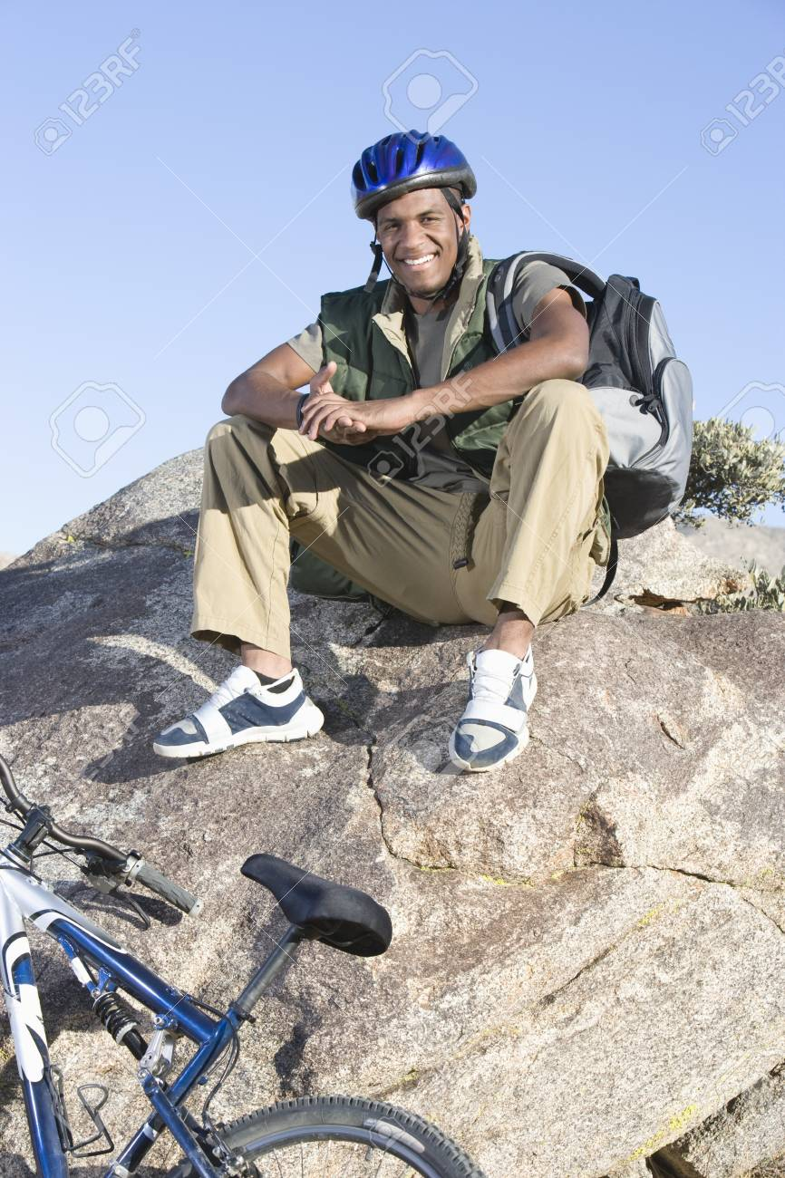 Man sits on rock wearing cycling helmet Stock Photo - 12547754