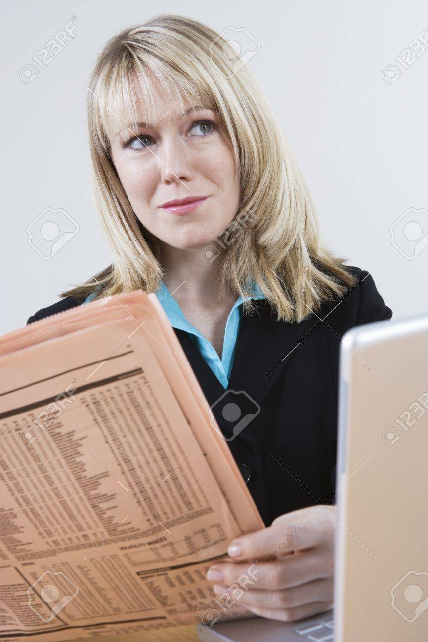 Businesswoman Reading Stock Listings in Newspaper Stock Photo - 12548539