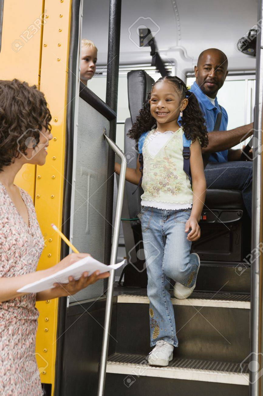 Teacher Unloading Elementary Students from School Bus Stock Photo - 12736376