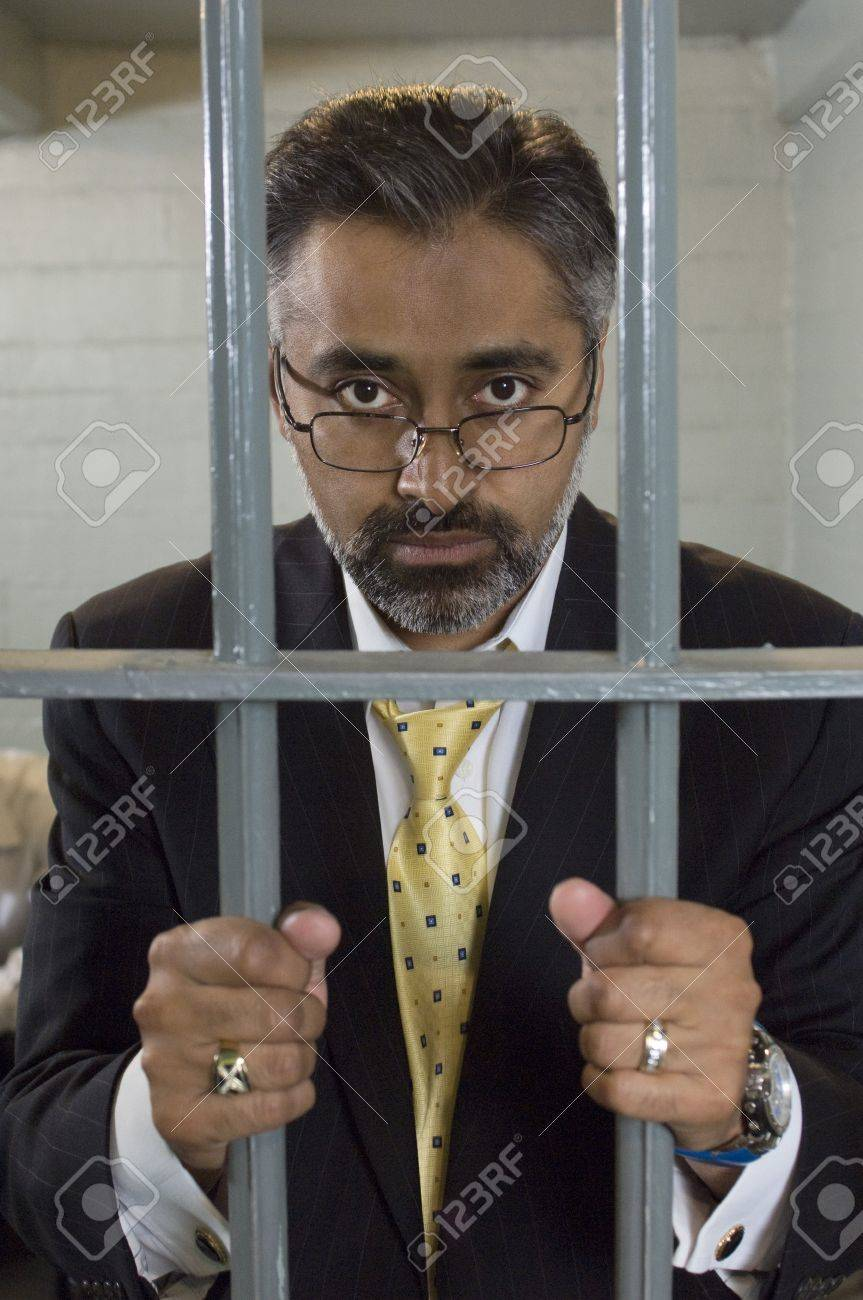 Businessman standing behind prison cell bars Stock Photo - 12736479