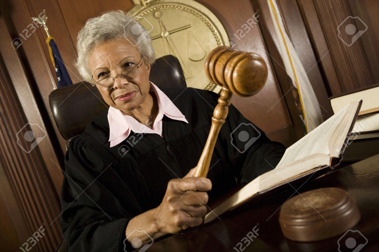 Female judge holding hammer in court - 12736678