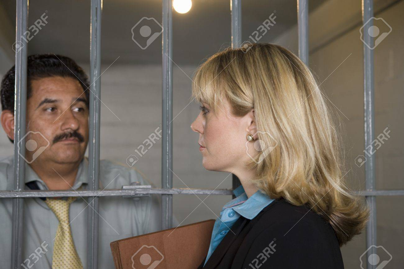Lawyer with criminal behind bars in jail Stock Photo - 12736699