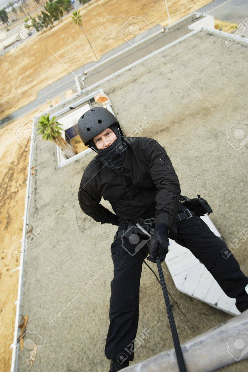 SWAT Team Officer Rappelling from Building Stock Photo - 12737065