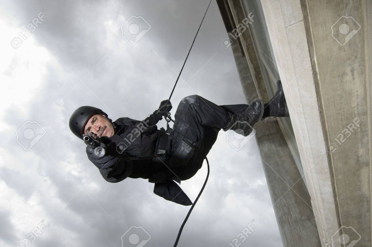 SWAT Team Officer Rappelling from Building Stock Photo - 12735681
