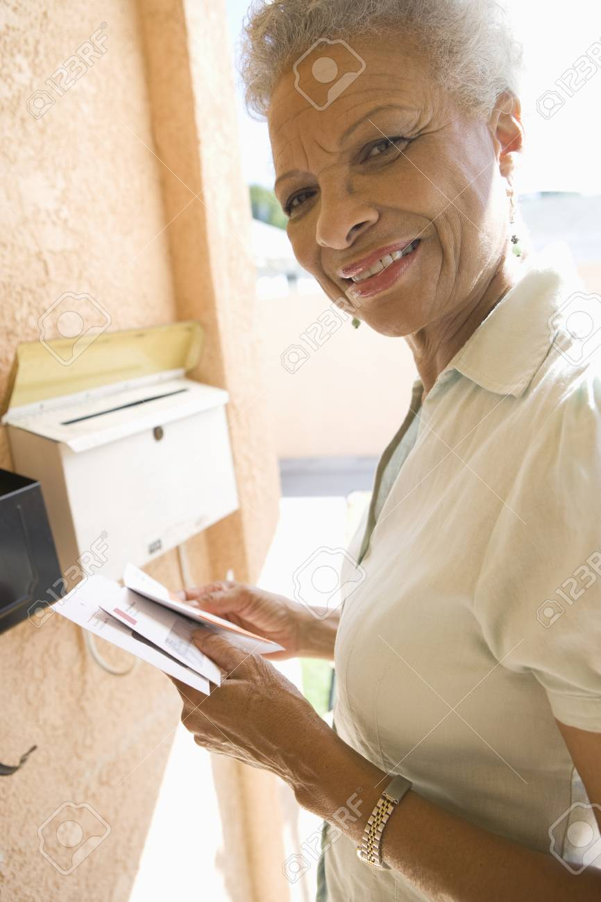 Woman collecting mail from letterbox Stock Photo - 12737522