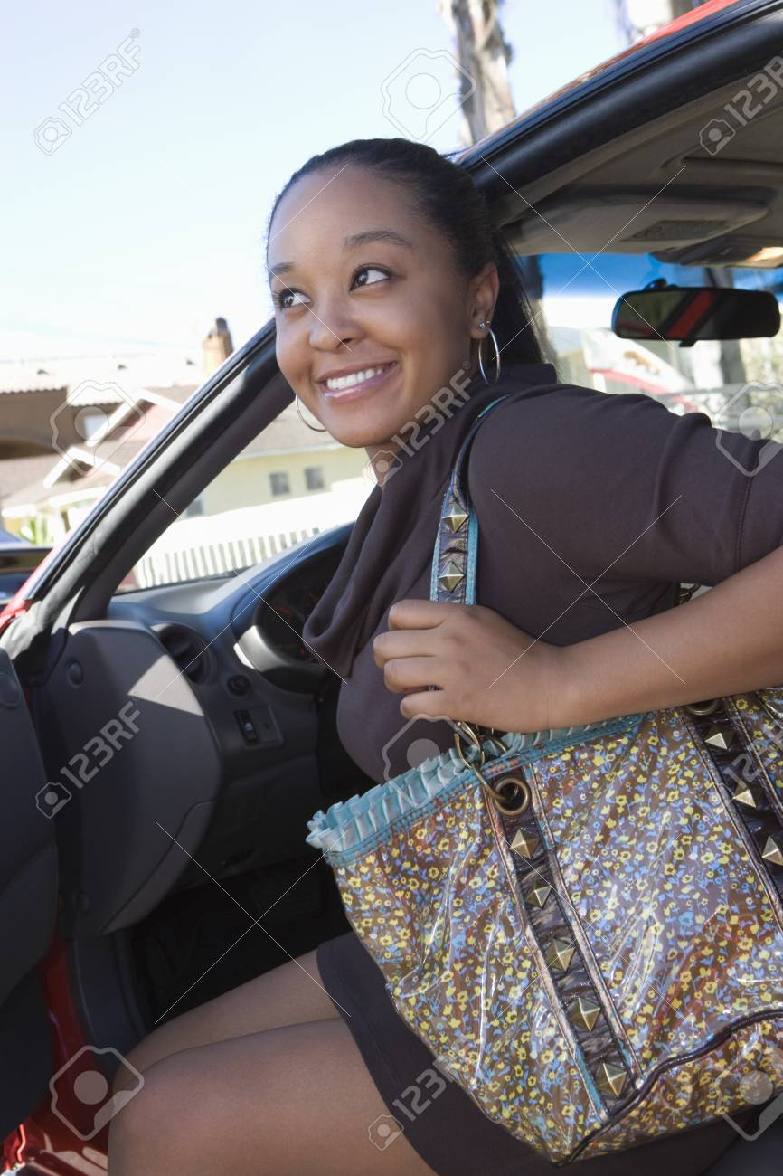 Young woman getting out of car Stock Photo - 12735572