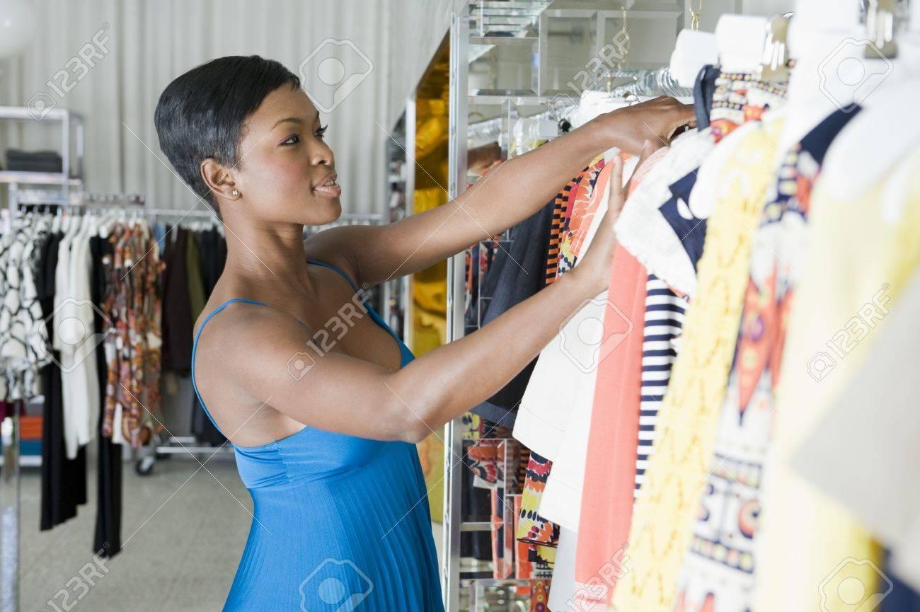 Woman looks through clothes rail Stock Photo - 12737565