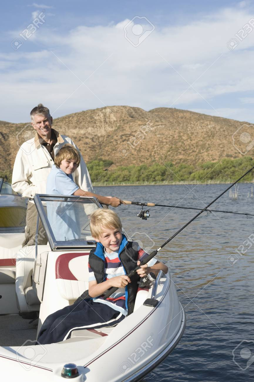 Father and sons fishing from a boat Stock Photo - 12737623