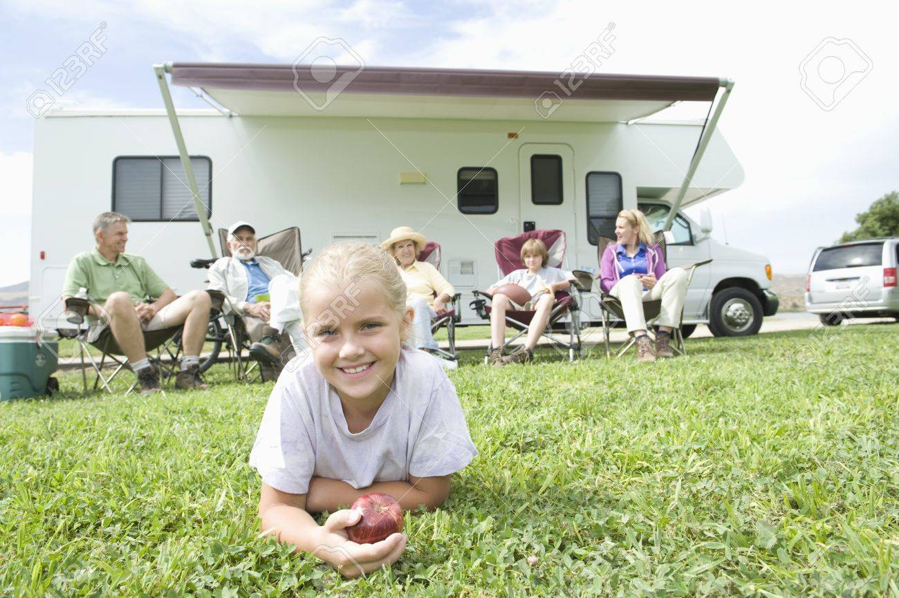 Girls eating an apple with family sitting outside RV home Stock Photo - 12737626