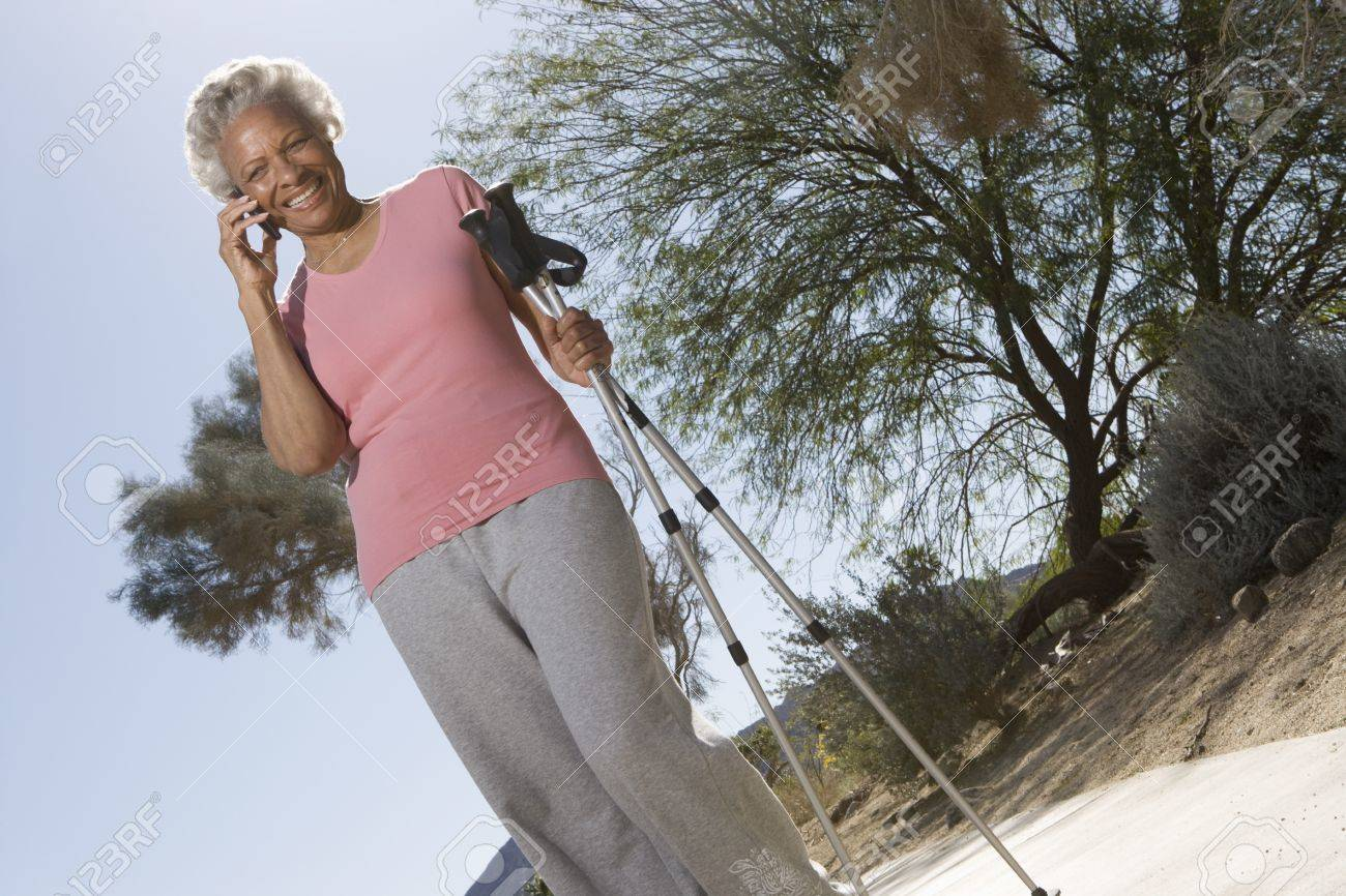 Senior woman stands on phone with walking poles Stock Photo - 12735649