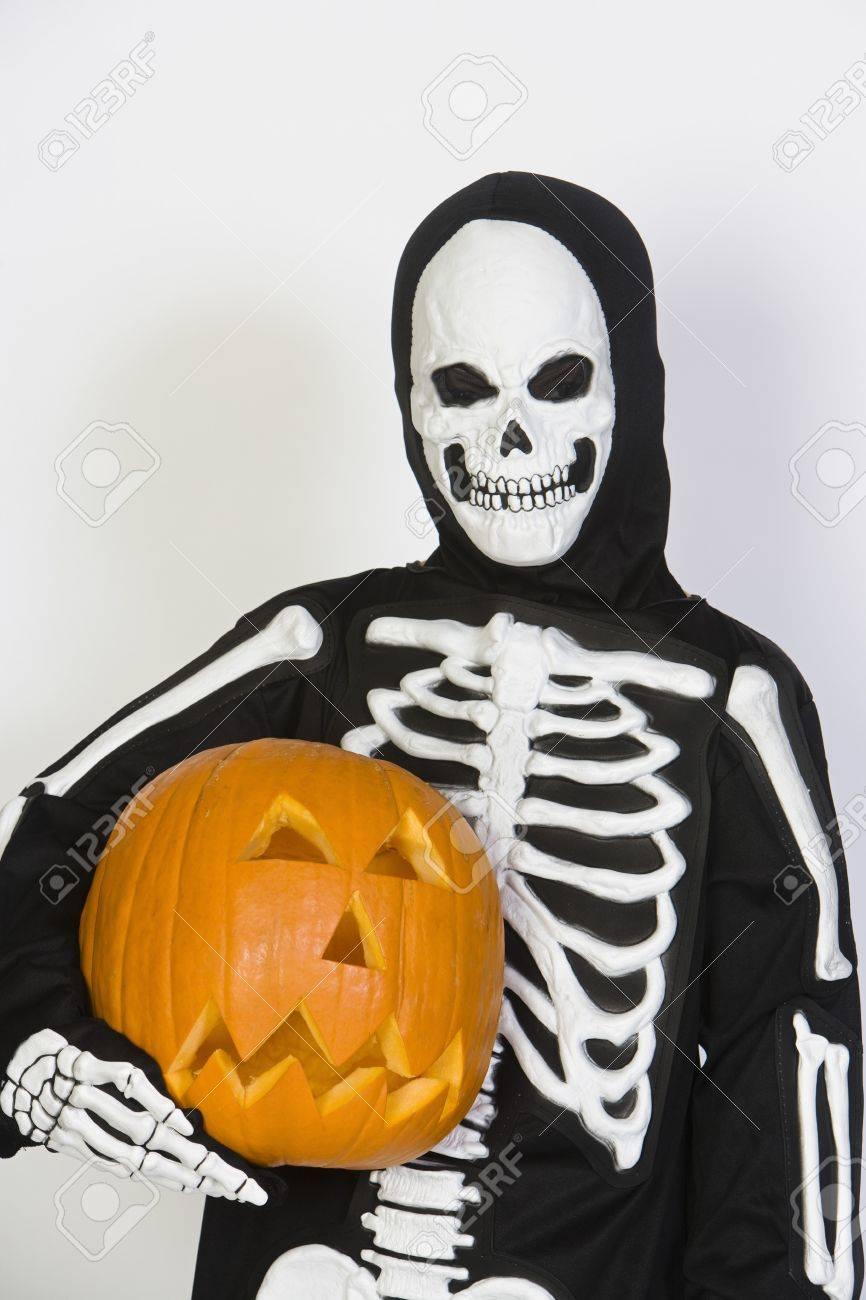 Portrait of child (7-9) wearing skeleton costume with jack-o-lantern Stock Photo - 12737698