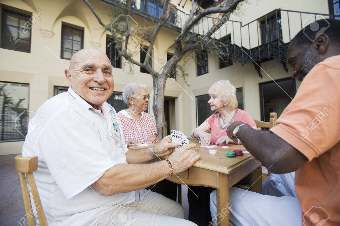 Senior people playing cards smiling Stock Photo - 12737721