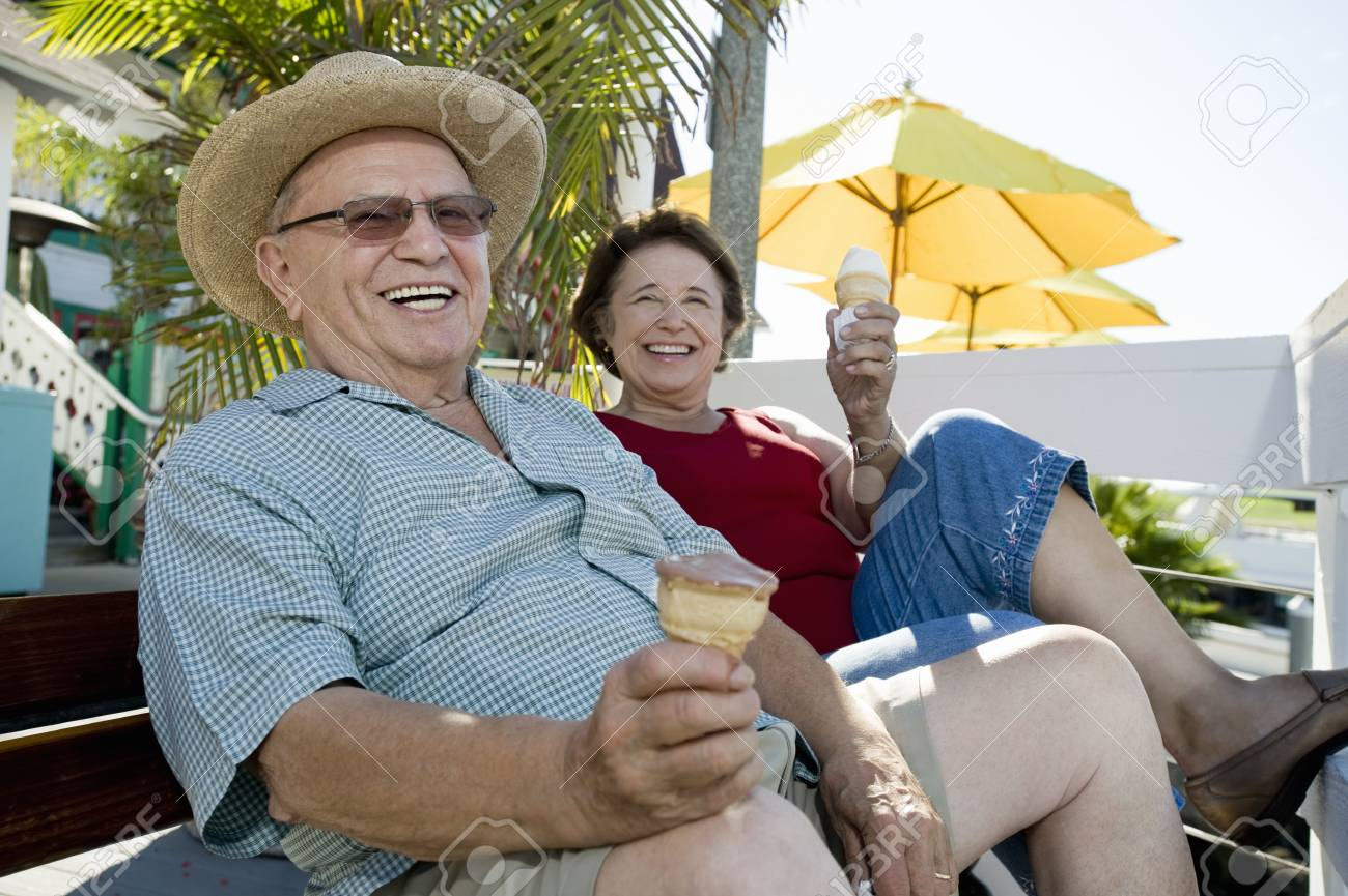 Senior couple sitting on bench and holding ice creams Stock Photo - 12737771