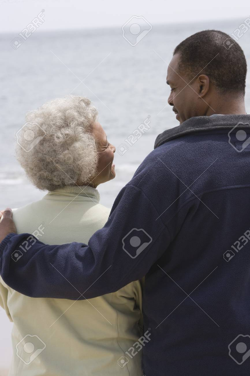 Man stands with his arm round a woman at waters edge Stock Photo - 12735546