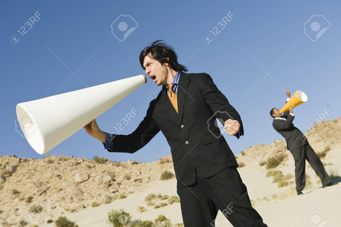 Two Businessmen Using Megaphones in Desert Stock Photo - 12735105