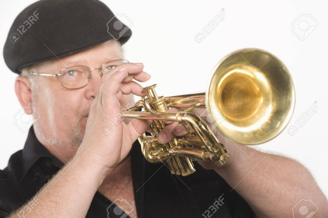 Mature man in flat cap playing the trumpet Stock Photo - 12735221
