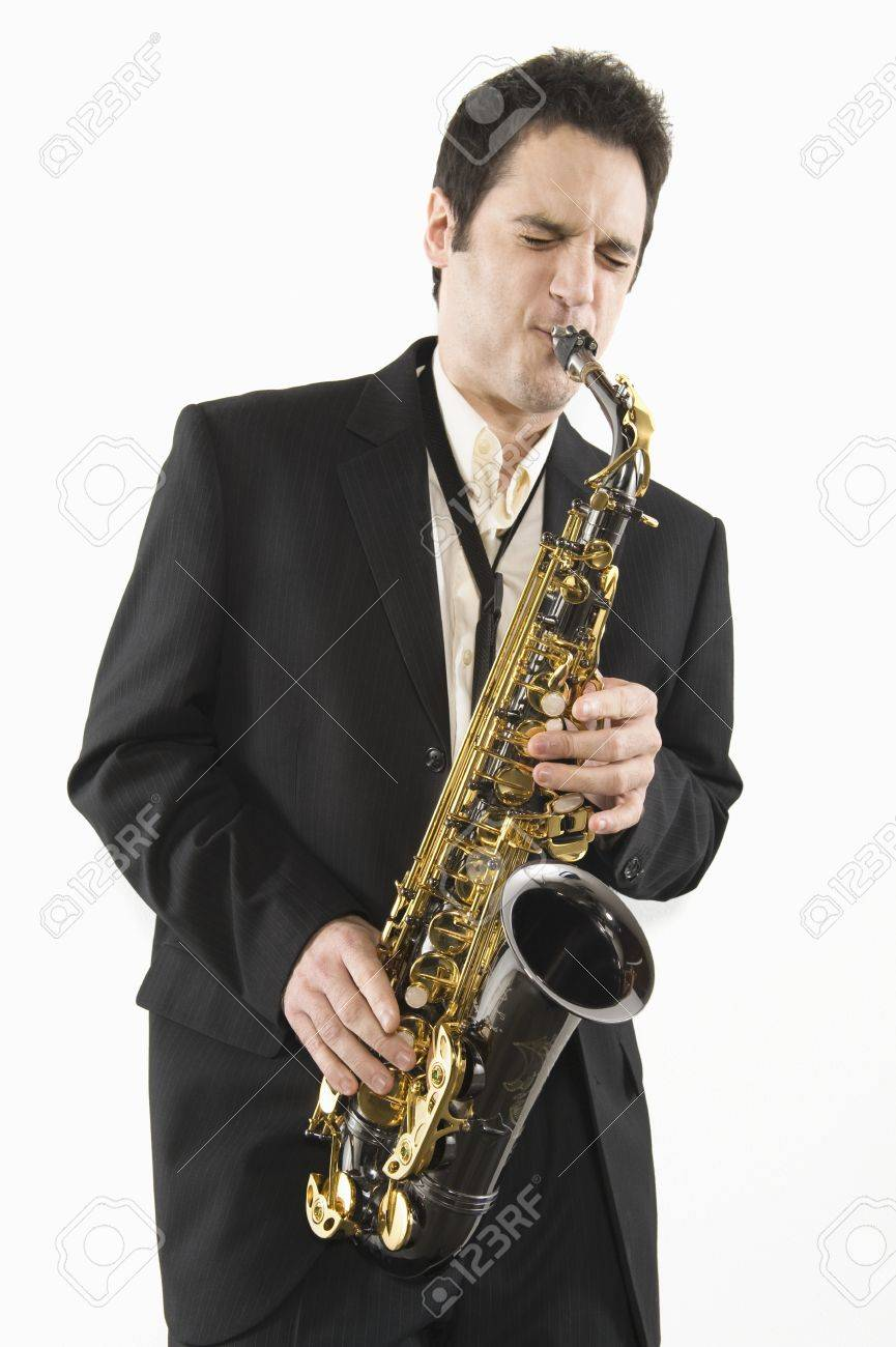 Mid adult man stands in suit playing the saxophone Stock Photo - 12735194