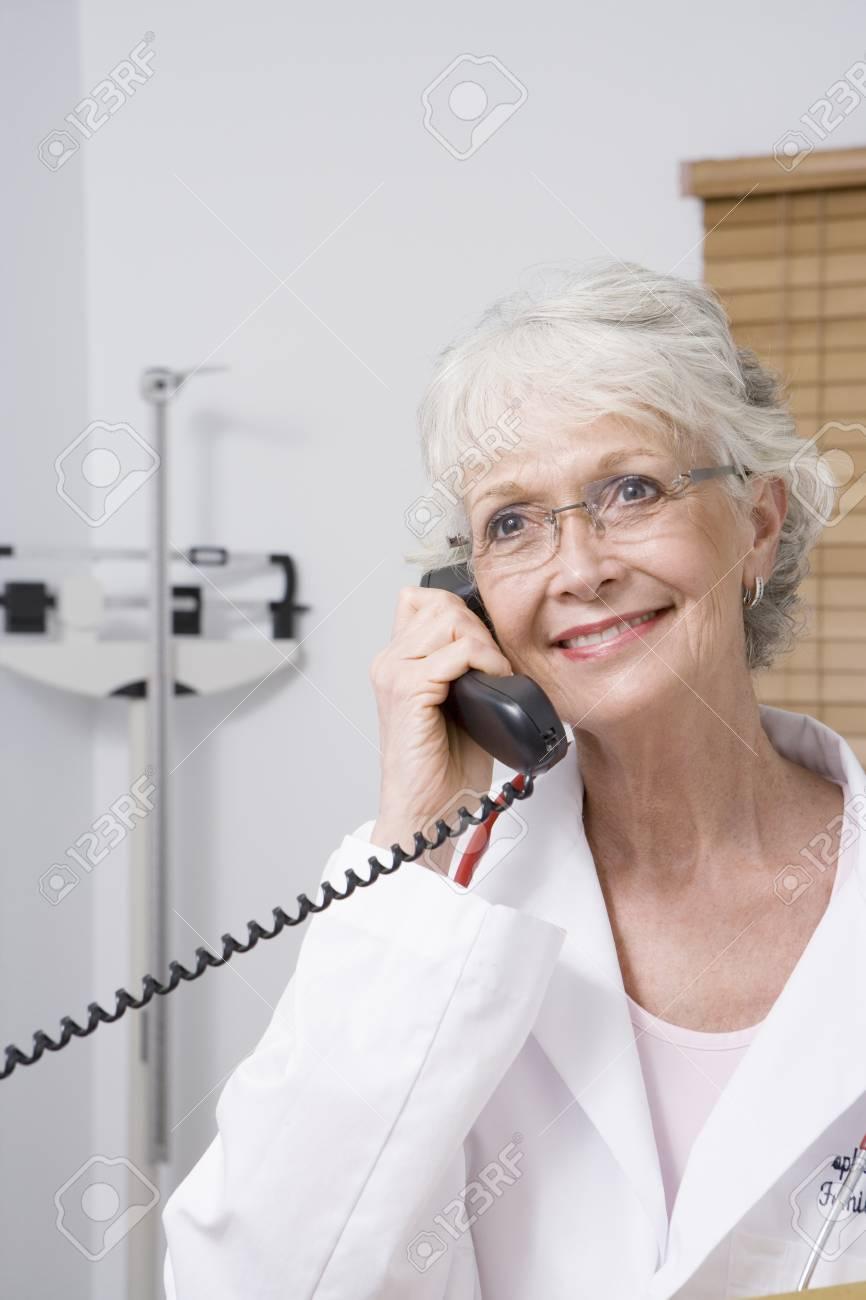 Senior healthcare professional holds telephone receiver Stock Photo - 12738028